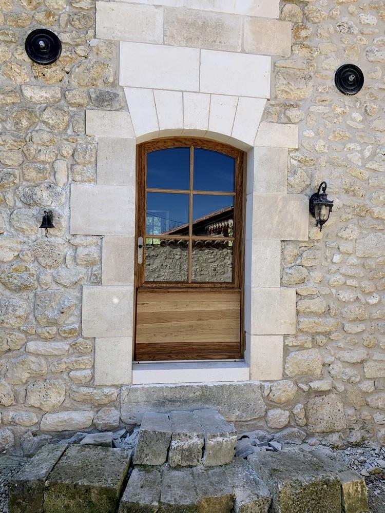 Porte d'entrée en arc surbaissé avec panneaux de soubassement à lames irrégulières gainées