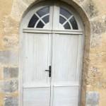 Porte d'entrée plein cintre avec fausse imposte à petits bois rayonnants et médaillon